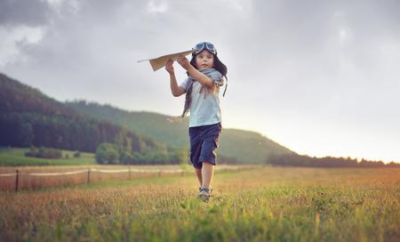 Mignon petit garçon jouant avion en papier