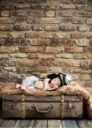 one parent: Little cute pilot sleeping on the suitcase
