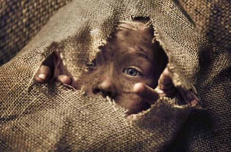 pobreza: Pequeño niño sin hogar que llevaba una bolsa Foto de archivo