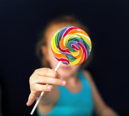 gotas de agua: Muchacha del jengibre que sostiene un lollipop dulce y colorido
