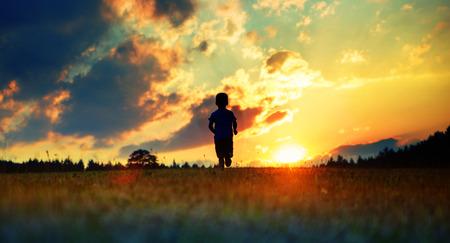 Bambino allegro che corre verso il tramonto photo