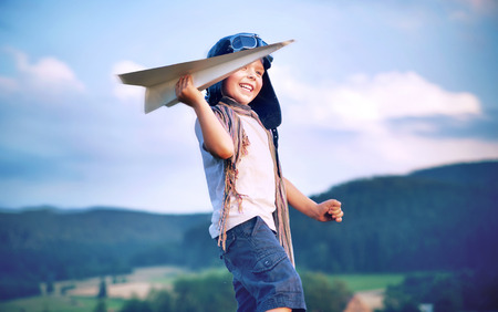 Alegre niño pequeño avión de papel del juguete Foto de archivo