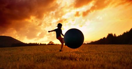 Piccolo bambino che gioca a calcio sul prato photo