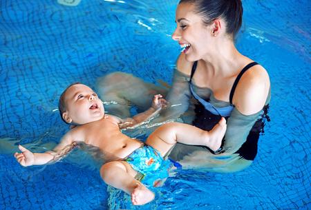 年輕的母親和可愛的寶寶在游泳池放鬆