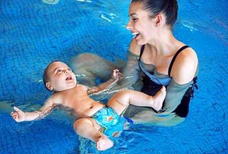 Yüzme havuzunda rahatlatıcı Genç anne ve sevimli bebek