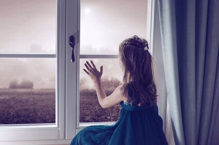 looking through window: Miserable child looking through window