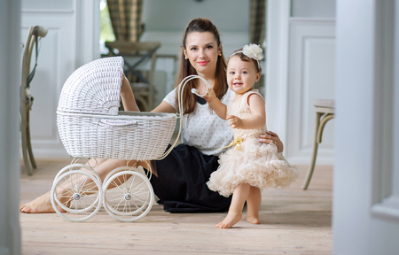 elegant girl: Mother watching her cute baby playing carriage Stock Photo