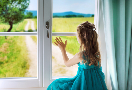 helplessness: Little sad girl looking through window