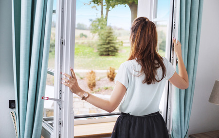 Elegant woman opening the bedroom window Stock Photo