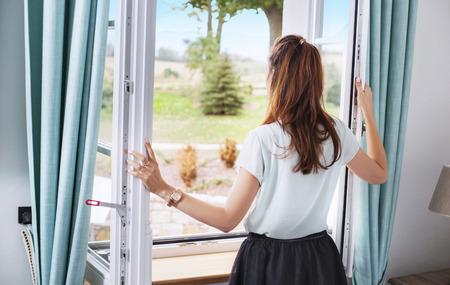 Elegante vrouw het openen van het raam van de slaapkamer