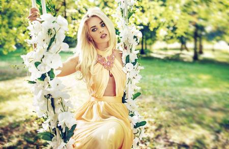 Phụ nữ tóc vàng xinh đẹp lắc lư trên bập bênh trang trí công phu