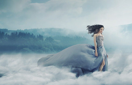 gown: Magical brunette lady on the foggy field