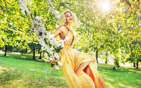 flower garden: Pretty young lady swinging in the middle of the garden