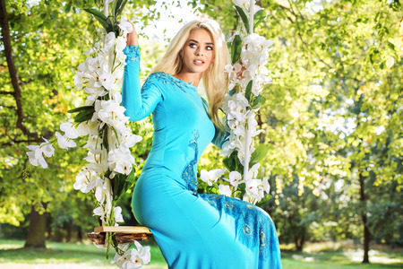 summer dress: Attractive blond woman on a flower swing in a park