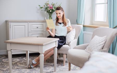 persona leyendo: Mujer elegante que lee un folleto interesante Foto de archivo