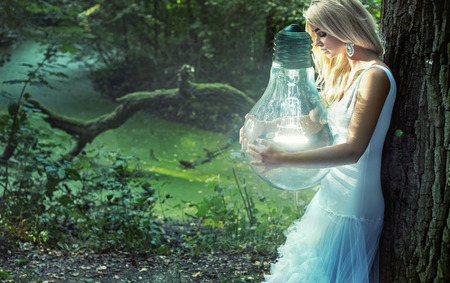 Stunning blond woman holding huge lightbulb Stock Photo