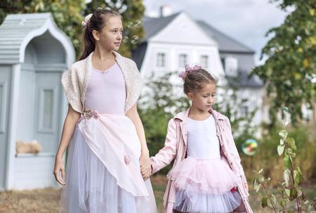 autumnn: Two cute sisters walking in the autumnn garden