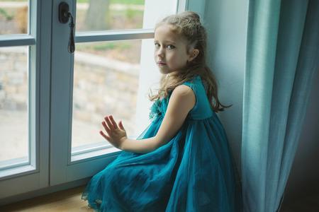 through window: Sad girl looking through window