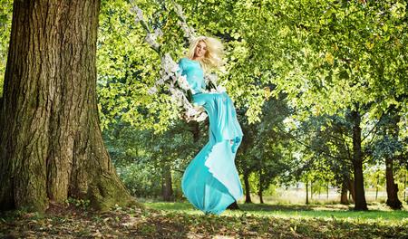 Splendida signora bionda su un altalena di fiori in un parco photo