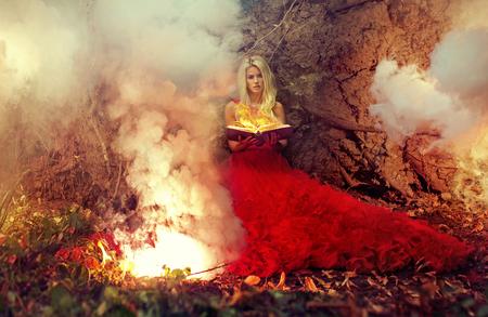 Blonde vrouw die het afvuren van magisch boek Stockfoto