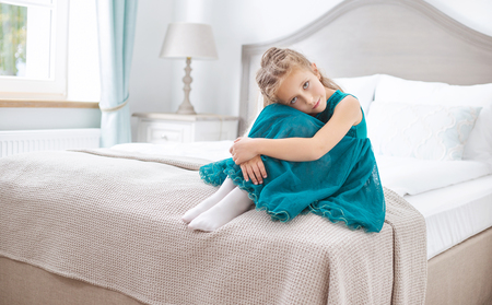 young female: Sad young girl sitting in the bedroom Stock Photo