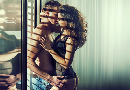 Sensual young couple in romantic hotels room Stock Photo