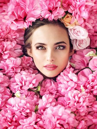 Bello fronte femminile tra i fiori di rosa photo