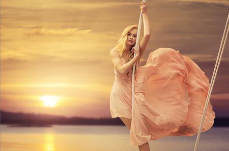 Hübsche Dame auf einer Schaukel über dem klaren Meer
