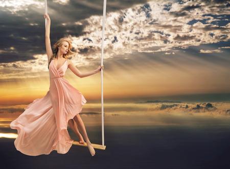 바다 위의 스윙에 매력적인 젊은 여자