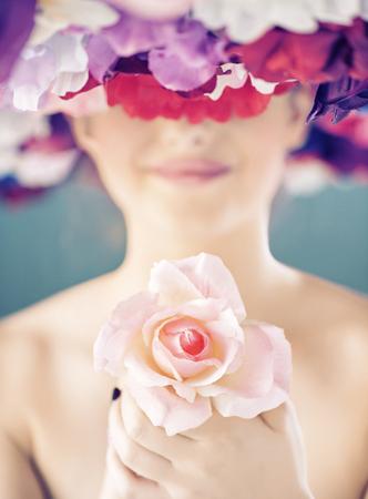 Donna graziosa che tiene una rosa rosa photo
