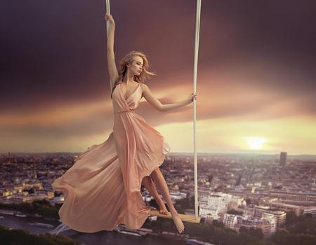 都市の上にぶら下がっているかわいい女性 写真素材