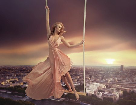 fantasy girl: Adorable woman dangling above the city Stock Photo