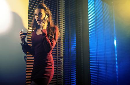 mujer bonita: Mujer joven curiosa que habla en el teléfono móvil