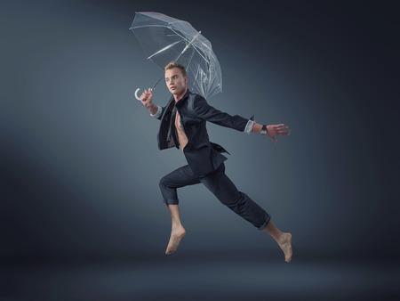 gerente guapo saltando con un paraguas transparente