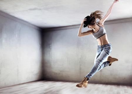 コンクリートの壁の背景にジャンプ運動の若いダンサー 写真素材