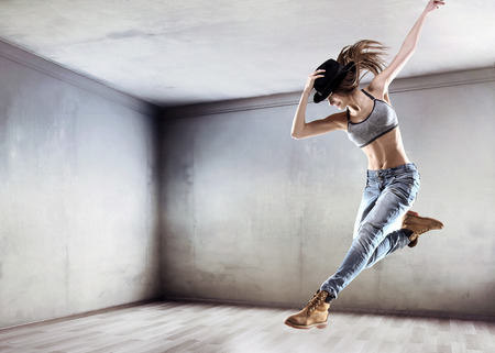 Athletic young dancer jumping on a concrete wall background