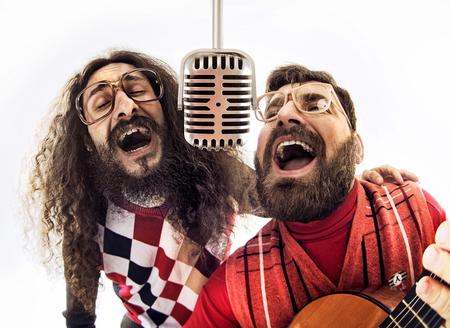 Dos muchachos nerdy cantando juntos Foto de archivo
