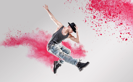 Portrait of a dancer excercising among a colorful powder Imagens