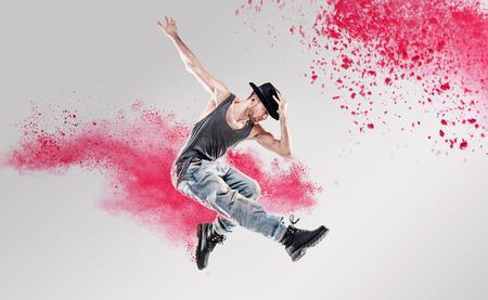 Retrato de un bailarín haciendo ejercicio entre un polvo colorido Foto de archivo