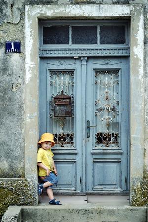 Ritratto di un piccolo bambino carino appoggiato su una porta retrò photo