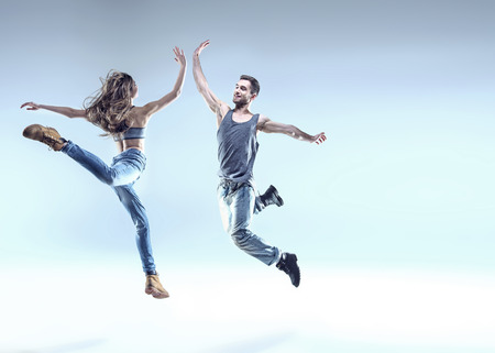 Two young breakdancers in a jumping pose