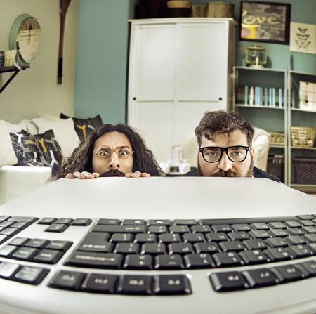 Два забавных ИТ-специалистов уставившись на той же раскладке Фото со стока