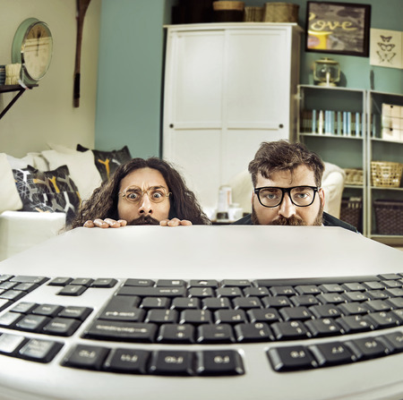 Two funny IT specialists staring at a keybord Фото со стока