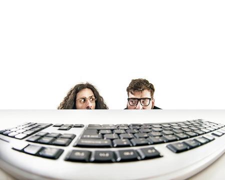 Twee grappige nerds staren naar een toetsenbord