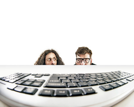 Two funny nerds staring at a keyboard Standard-Bild