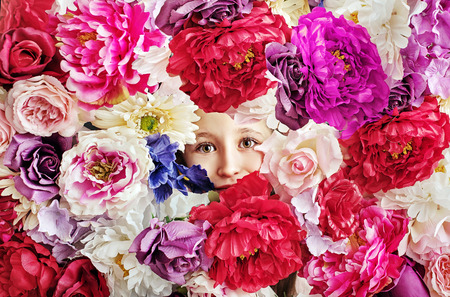 petites fleurs: image conceptuelle de la petite fille derrière un mur de fleurs Banque d'images