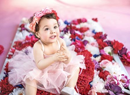 niñas pequeñas: chica linda sentado en un ramo de flores