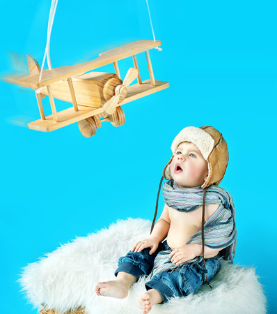 wooden toy: Cute baby boy with an vintage toy airplane