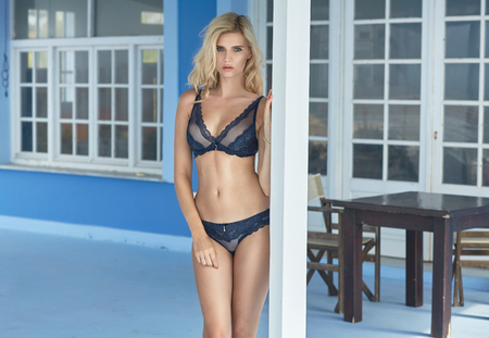 Alluring blond lady posing on hotel terrace