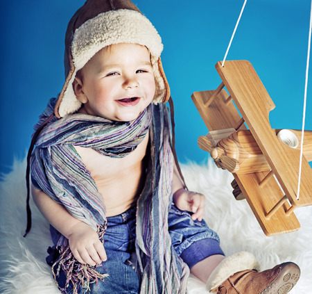 babies with toys: Laughing small boy with a toy airplane
